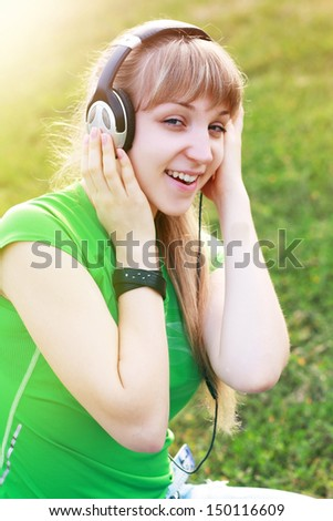 Woman listening to music. Female student girl outside in park listening to music on headphones while studying. Happy young university student