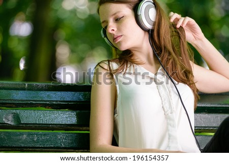 Woman listening to music. Female student girl outside in park listening to music on the headphones