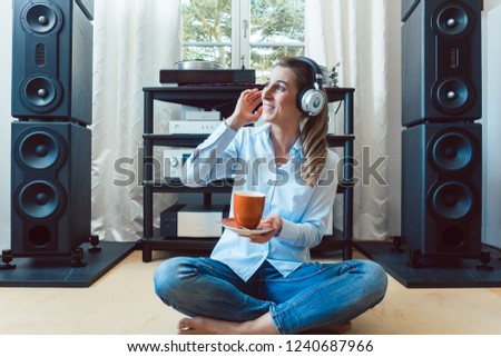 Woman listening to music from a Hi-Fi stereo at home