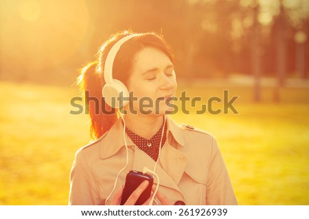 Woman listening to music in headphones in park  in sunlight in a sunny day. Young smiling businesswoman,student ,professional outdoors listening to music. Businesswoman smiling,Life style,