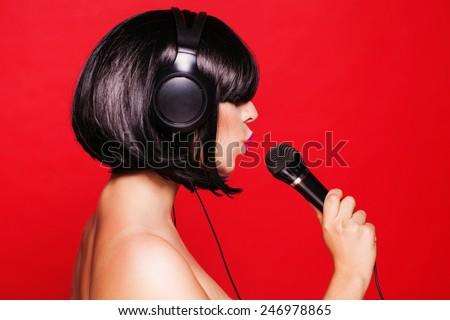 Woman listening to music on headphones enjoying a dance. Closeup portrait of beautiful girl with pink lips
