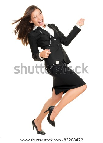 Woman listening to music on mp3 player, dancing playing air guitar. Funny happy portrait of business woman isolated on white background in full length.