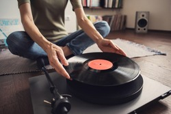 Woman listening to music, relaxing, enjoying life, having fun on home party. Turntable playing vinyl LP record. Leisure, lockdown, retro revival, hobby, lifestyle concept