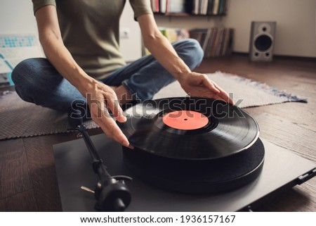 Woman listening to music, relaxing, enjoying life, having fun on home party. Turntable playing vinyl LP record. Leisure, lockdown, retro revival, hobby, lifestyle concept Stockfoto ©