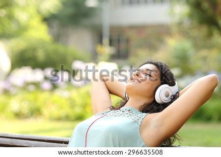 Woman listening to music with headphones and relaxing in a park