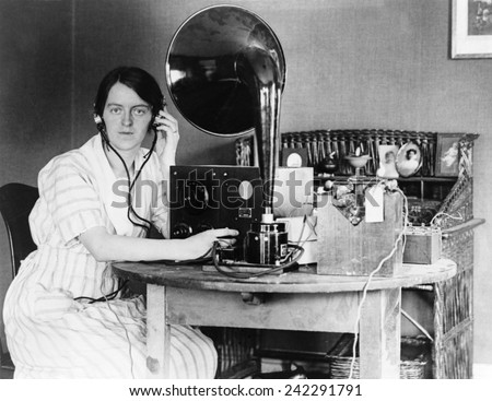 Woman listening to radio in her home receiving a personal radio message telling her when her husband will arrive home. 1922.