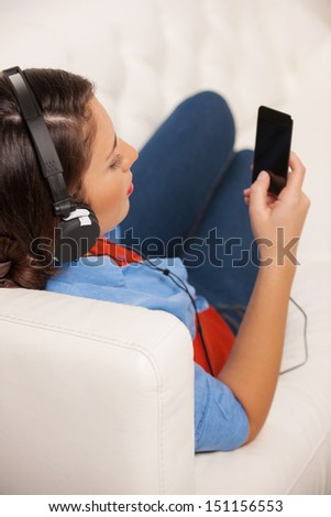 Woman listening to the music. Rear view of beautiful young woman in headphones listening to the music
