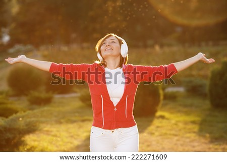 Woman lit by the rays of the evening sun at sunset. Good mood, favorite music, happy time, autumn. Ok. Woman with headphones listening to music on her head. Woman on the nature of urban clothing.