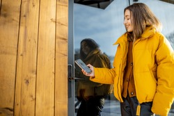 Woman locking smartlock on the entrance door using a smart phone. Concept of using smart electronic locks with keyless access