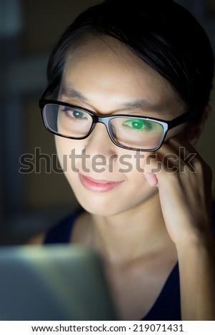 Woman look at computer screen at night