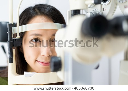 Woman look at ophthalmoscope in eye clinic