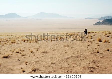 Woman look at the desert - Desert Mountains background. Namibia, Deadvlei, Sossuvlei.