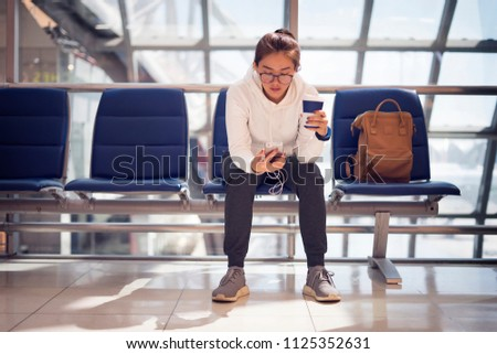 Woman looking and checking her flight time on smart phone mobile in the airport terminal and drinking coffee while waiting for her flight on travel trip. Female passenger at terminal, indoors. #1125352631