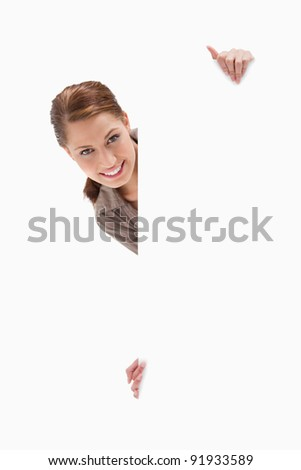 Woman looking around blank sign against a white background
