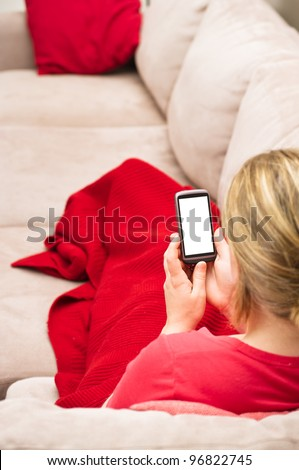 Woman looking at a blank generic smartphone while sitting on a couch. Useful for video calling or other browsing activity.