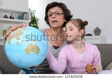 Woman looking at a globe with her granddaughter