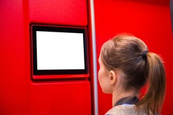 Woman looking at blank digital interactive white display on red wall at exhibition or museum with futuristic scifi interior. White screen, mock up, copyspace, template, technology concept