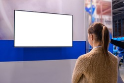 Woman looking at blank digital interactive white display wall at exhibition or museum with futuristic scifi interior. White screen, mock up, future, copyspace, template, technology concept