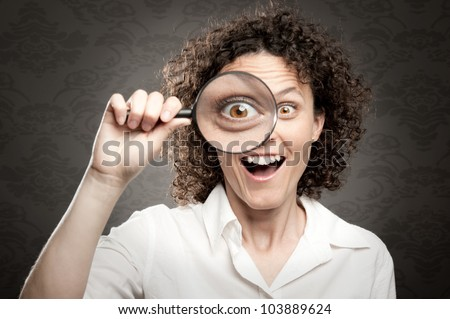 woman looking at camera through magnifying glass