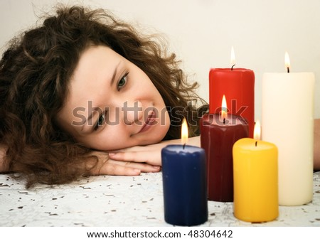 woman looking at candles with head over hands