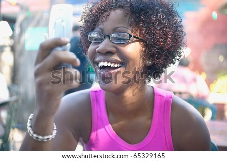 Woman looking at cell phone while laughing