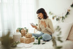 Woman looking at christmas letter. Woman sitting on bed at home with christmas presents and mails.
