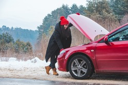 woman looking at engine broken car at winter road side