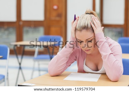 Woman looking at exam paper anxiously in exam hall