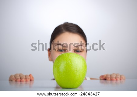 Woman looking at green apple on the table, focus on apple