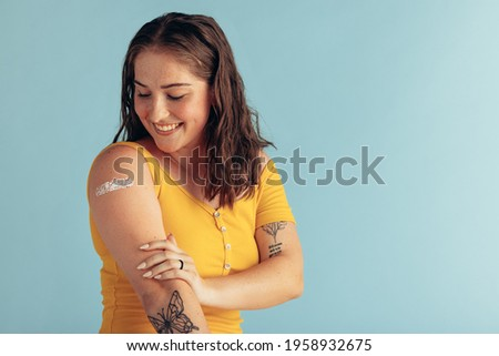 Woman looking at her arm with band-aid after receiving vaccine dose. Woman getting vaccination.