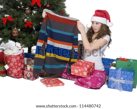 Woman looking at her Christmas present and making a face while  sitting near Christmas tree