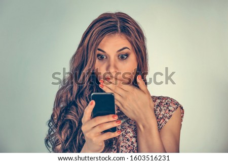 Woman looking at her phone with shocked expression on face covering mouth in shock. Mixed race model isolated on light green background with copy space. Horizontal image.