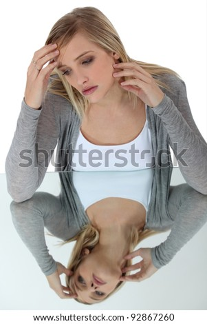 woman looking at her reflexion in a glass table