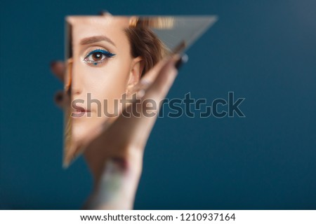 Woman looking at her self reflected in a mirror, selfie, vanity, conceit, ego, digital narcissism concept minimal flat design. An illusion, beautiful girl with a mirror in her hands