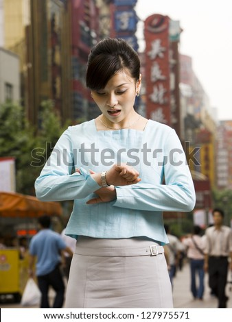 Woman looking at her watch in disbelief.