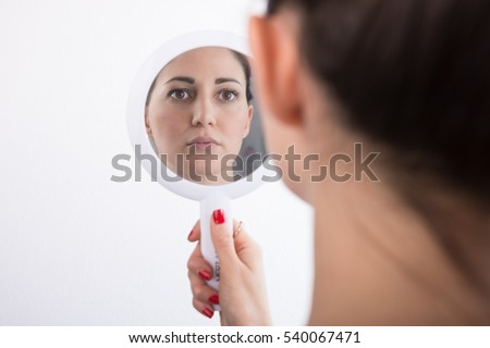 woman looking at herself in the ...