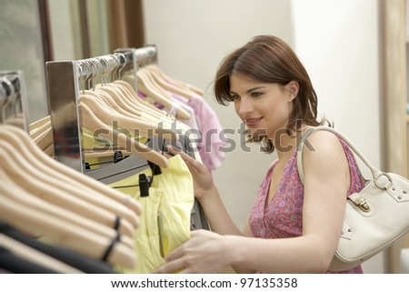 Woman looking at line of clothes hanging in a fashion store. - stock photo