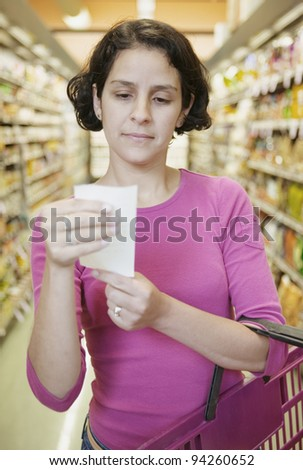 Woman looking at list in grocery store