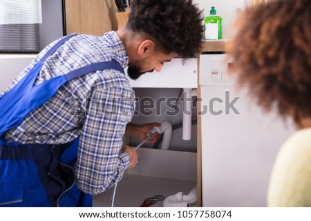 Woman Looking At Male Plumber Cleaning Clogged Pipes - Shutterstock ID 1057758074