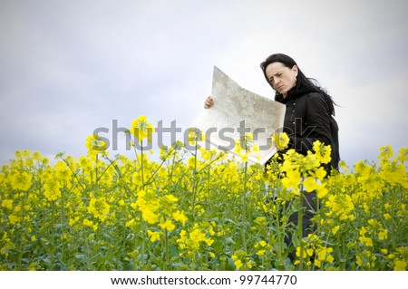 woman looking at map standing in field full of flowers