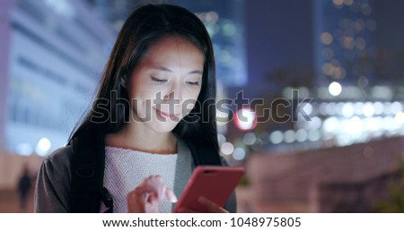 Woman looking at mobile phone in the evening  #1048975805