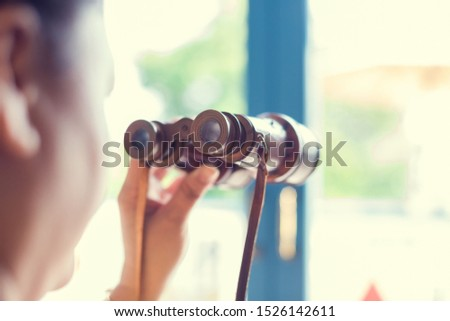 Woman looking at old binoculars to windows. Summer day. See the goal, look forward with pleasure to travel.