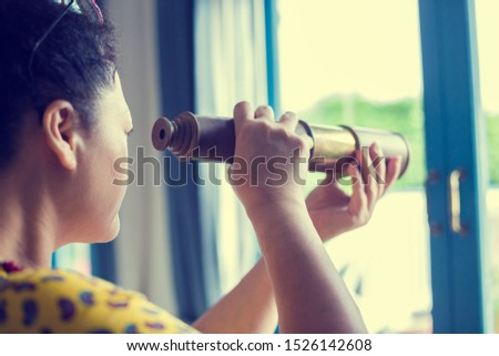 Woman looking at old telescope to windows. Summer day. See the goal, look forward with pleasure to travel.
