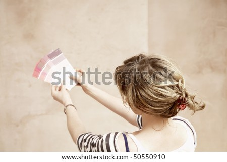 Woman looking at paint colour swatches in unrenovated room, back view