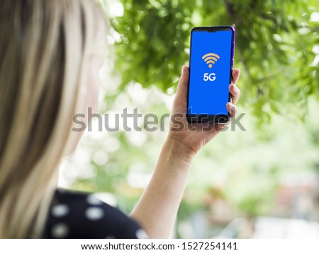 Woman looking at phone screen with 5g on screen