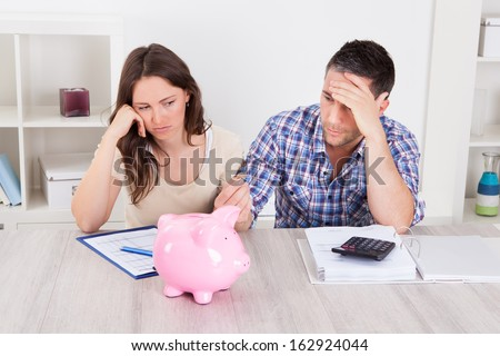 Woman Looking At Piggybank Raised By Young Man Stock photo ©