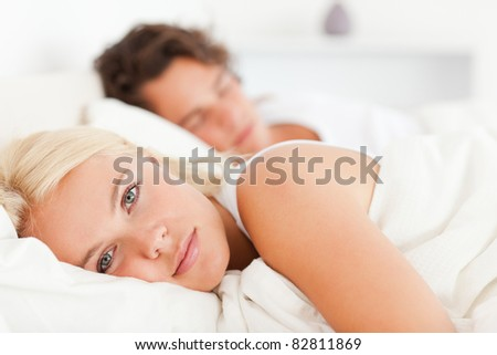 Woman looking at the camera while her fiance is sleeping in their bedroom