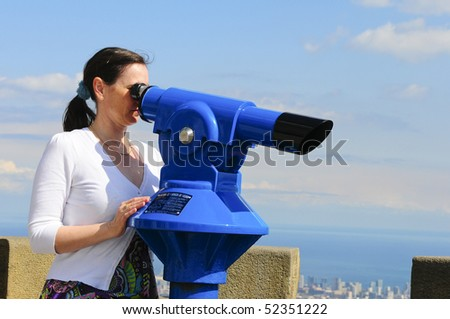 Woman looking at the city of Barcelona from Tibidabo, using a coin operated pair of binoculars. #52351222
