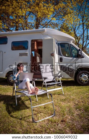 Woman looking at the laptop near the camping . Caravan car Vacation. Family vacation travel, holiday trip in motorhome RV. Wi-fi connection information communication technology. #1006049032