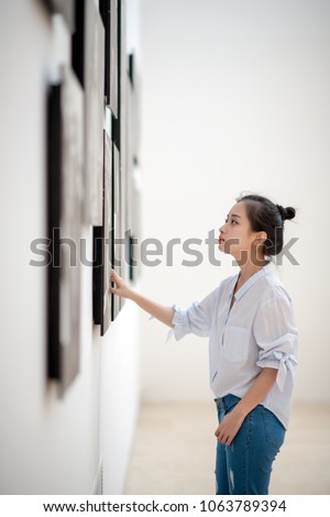 woman looking at the pictures on the wall #1063789394